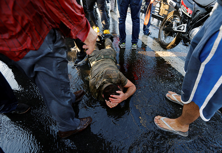 Un soldado se protege de la multitud después de que las tropas implicadas en el intento de golpe de Estado se rindieran en el Puente Bósforo, en Estambul