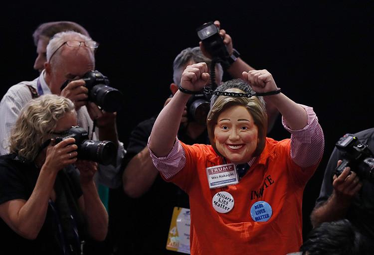 Un delegado porta una máscara de Hillary Clinton, así como unas esposas y un mono de preso, antes del inicio del último día de la Convención Nacional Republicana en Cleveland, Ohio (EE.UU.).