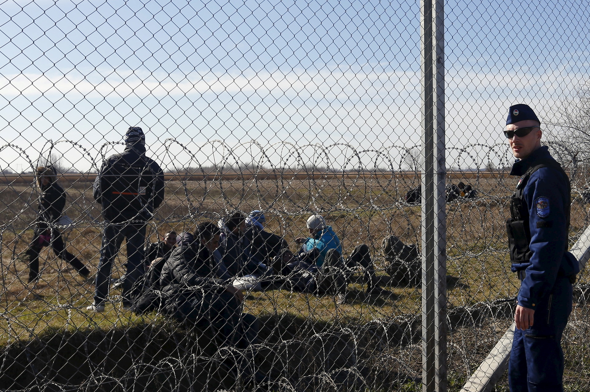 Un policía húngaro y un grupo de refugiados cerca de una valla en la frontera serbio-húngara en Morahalom, Hungría, 22 de febrero de 2016