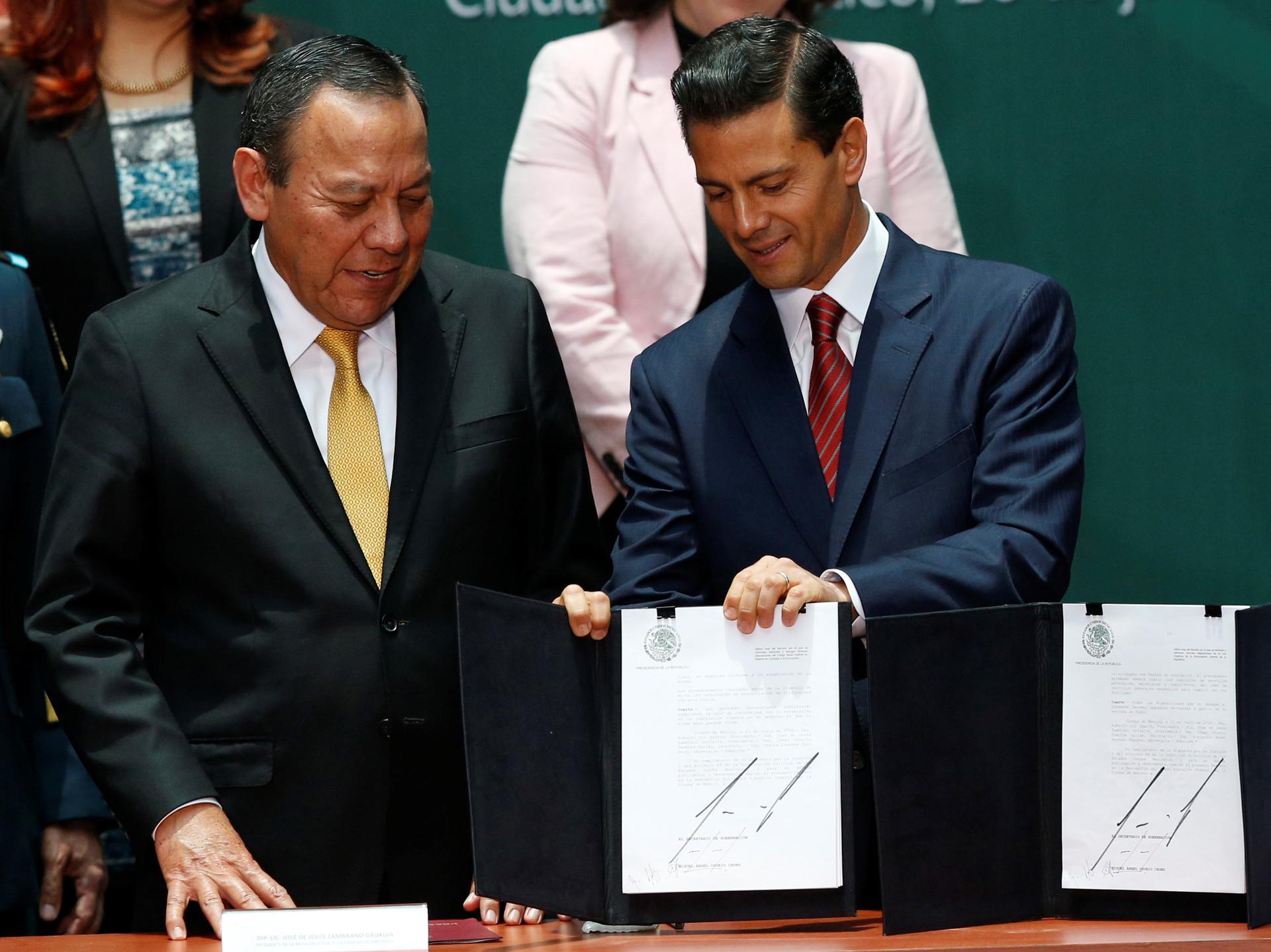 El presidente de México, Enrique Peña Nieto, entrega documentos al congresista mexicano Jesús Zambrano durante la promulgación de la Ley Nacional Anticorrupción, el 18 de julio de 2016.
