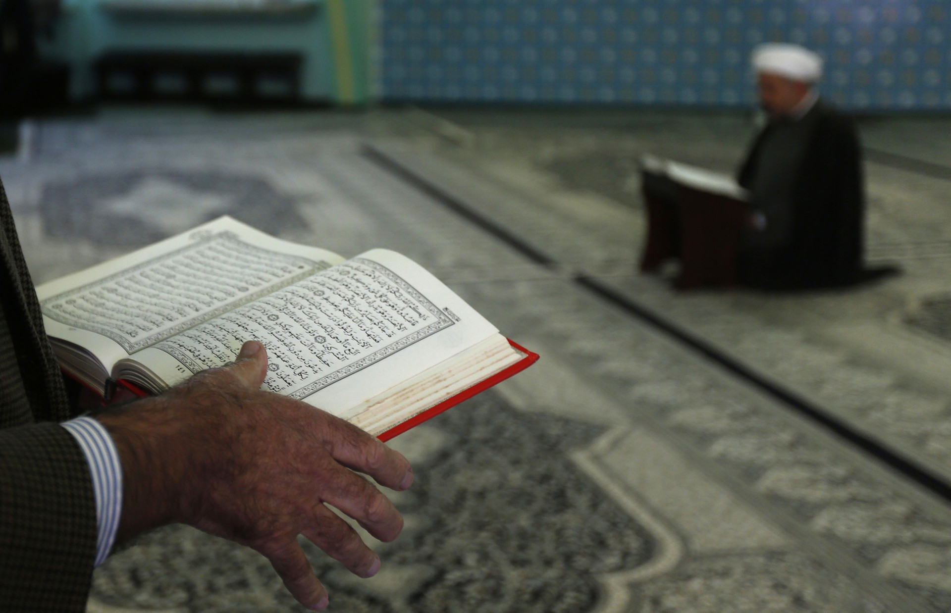 Un hombre lee el Corán en una mezquita