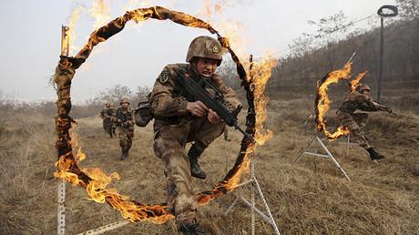 Soldados del Ejército Popular de Liberación atraviesan de un salto un obstáculo en llamas durante un entrenamiento en una base militar en Tianshui, provincia de Gansu, China, el 6 de enero de 2016.