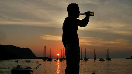 Un turista toma una cerveza durante la puesta de sol en la playa Benirrás de Ibiza