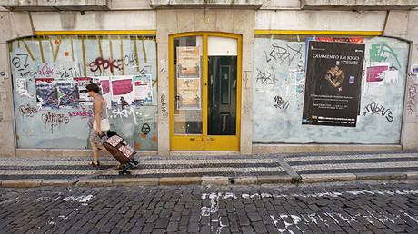 Una mujer pasa por delante de una tienda cerrada en el centro de Lisboa, Portugal