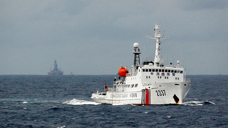 Un buque de la Guardia Costera china pasa cerca de la plataforma petrolera china, Haiyang Shi You 981, en el mar de la China Meridional, el 13 de junio de 2014.