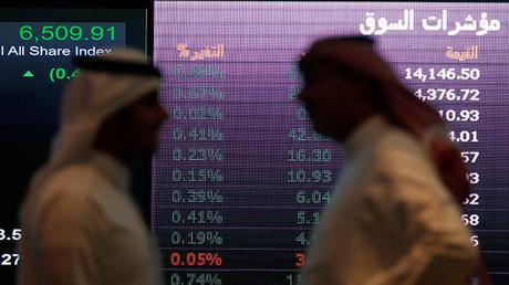 Dos inversores hablan mientras controlan una pantalla con información de la bolsa de valores Tadawul de Riad, Arabia Sautita.