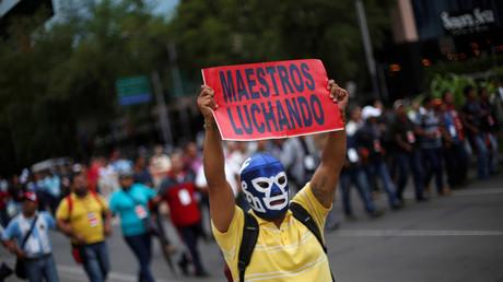 Una manifestante de la Coordinadora Nacional de Trabajadores de la Educación ( CNTE ) sindicato de maestros tiene una señal mientras marcha contra la reforma educativa del presidente Enrique Peña Nieto en la avenida Reforma en la Ciudad de México , México , 11 de julio de 2016.