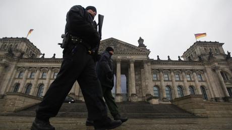 Oficiales de policía alemanes caminan frente del Reichstag en Berlín.