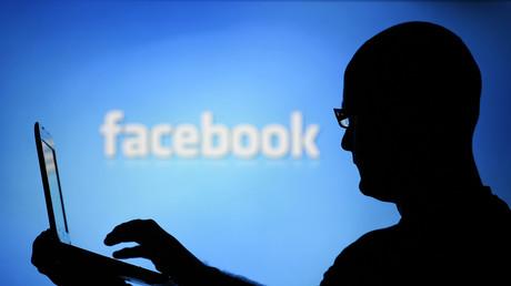 La silueta de un hombre con una portátil vista sobre una pantalla con un logotipo de Facebook, Zenica, Bosnia y Herzegovina