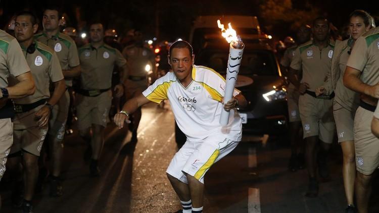 Sandro Testinha patina con llama olímpica en sus manos.