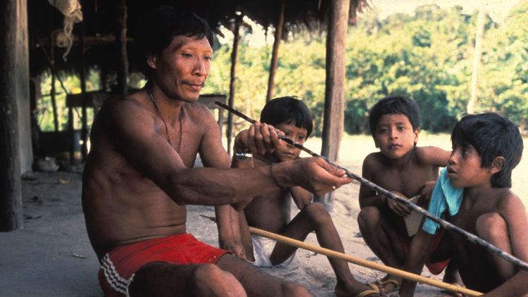 Un indígena Waimiri-atroari enseña a niños cómo hacer una flecha