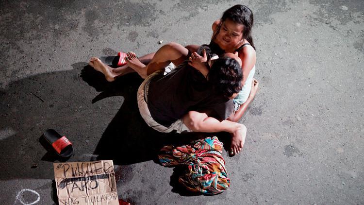 Una mujer junto al cuerpo de su pareja, muerto en una serie de asesinatos relacionados con las drogas en la ciudad de Pásay, Filipinas