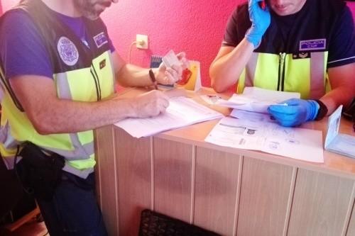 Agentes revisando la documentación intervenida en el local tras las detenciones.