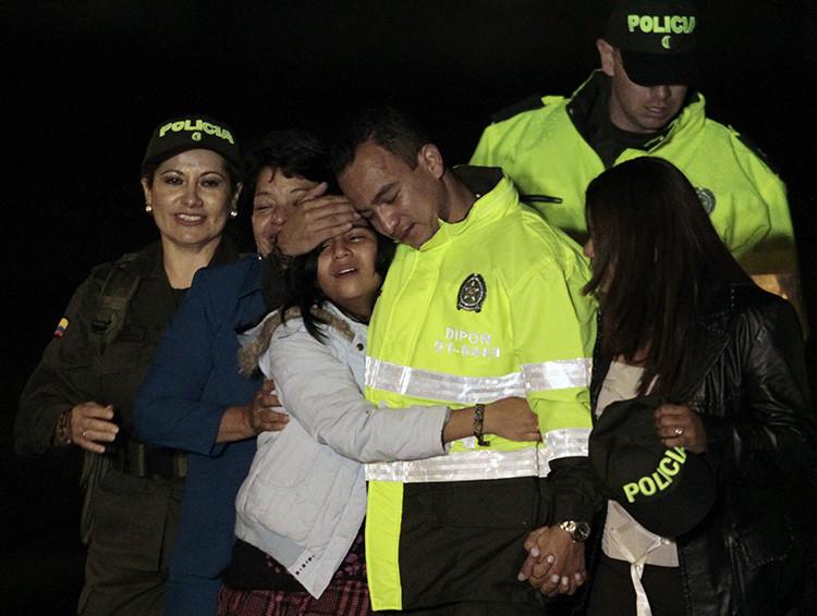 El policía colombiano Carlos Alberto Ocampo abraza a su familia llegando al aeropuerto de la Armada, después de haber sido liberado como rehén por los rebeldes de las FARC el 13 de febrero de 2011.