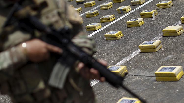 Un oficial de policía hace guardia como paquetes de cocaína incautada se muestran durante una presentación a los medios en la base naval.