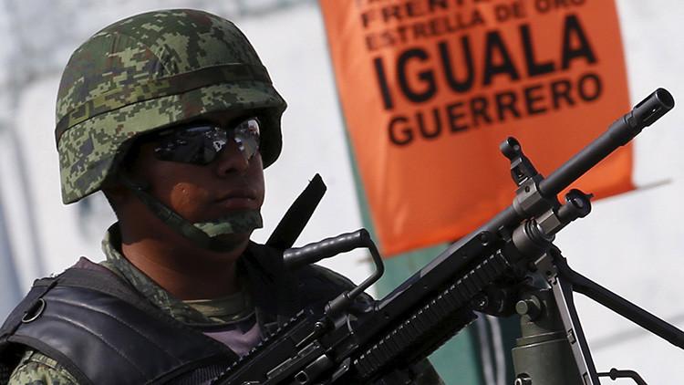 Un soldado monta guardia encima de un vehículo durante la ceremonia de Día de la Bandera en Iguala, estado mexicano de Guerrero.
