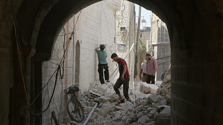 Residentes examinan sus viviendas dañadas después de un ataque aéreo en Alepo, Siria.