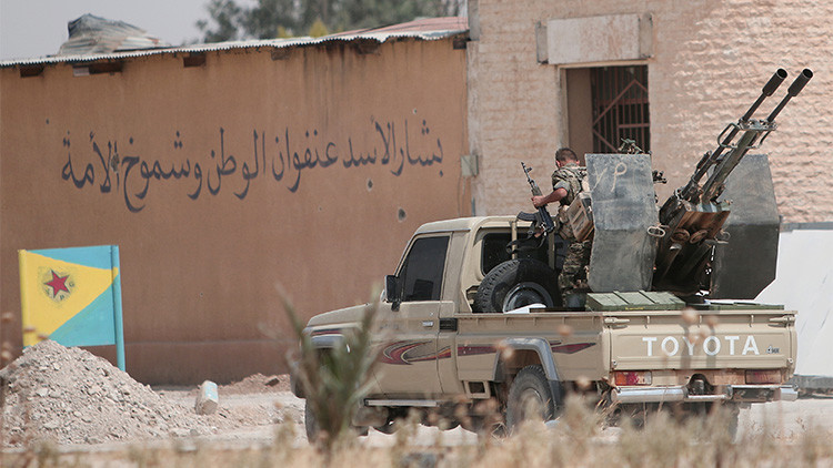 Un combatiente kurdo de las Unidades de Popular Protección (YPG) en una camioneta con un arma antiaérea en Hasaka, Siria.