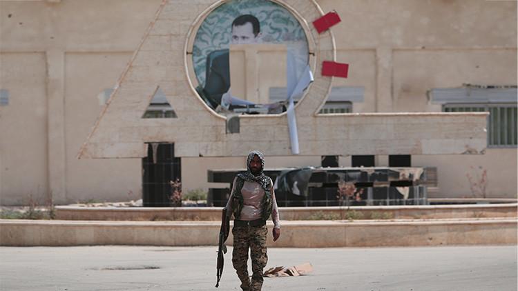 Un combatiente kurdo de las Unidades de Protección Popular (YPG) con una imagen desfigurada del presidente sirio Bashar al Assad en el fondo, en la ciudad siria de Hasaka.