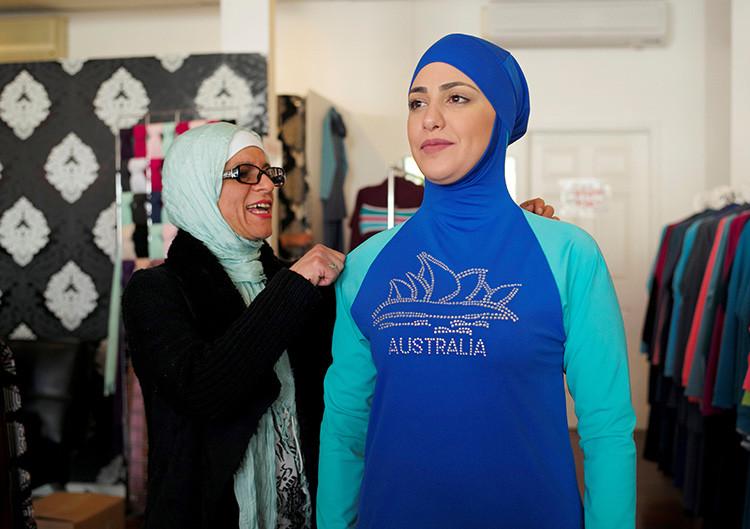 La diseñadora que creó el 'burkini', Aheda Zanetti (izquierda), ajusta uno de estos trajes de baño a la modelo Salwa Elrashid en su tienda de moda en Sídney, Australia.