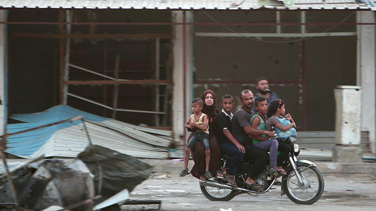 Miembros de una misma familia huyen en una motocicleta por la ciudad de Hasakah, Siria, el 20 de agosto de 2016.