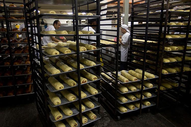 Trabajadores llevan bandejas de pan de jamón en una pastelería, Caracas, Venezuela, el 31 de diciembre de 2011.