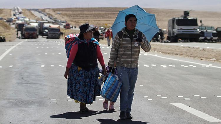 Los pasajeros de un autobús caminan por la carretera bloqueada por los mineros en Panduro