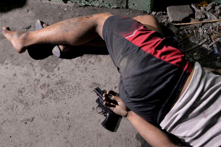 El cuerpo de un hombre con una pistola bajo su mano, quien según la policía murió durante un operativo de incautación de droga en Manila, Filipinas