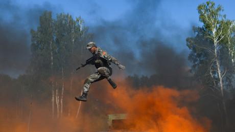 Un soldado del Ejército chino salta encima de las llamas durante una prueba