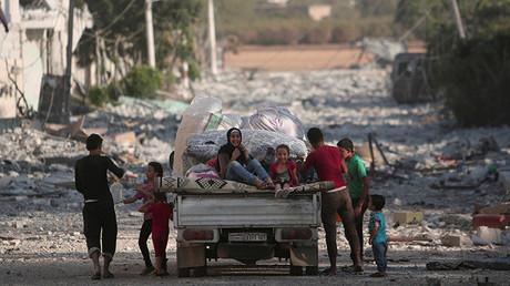Niños en una camioneta cargada con sus pertenencias en Manbij, provincia de Alepo, Siria
