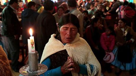 Una mujer aymara reza en la iglesia durante la celebración de la Virgen de Urkupina en La Paz, 15 de agosto de 2016