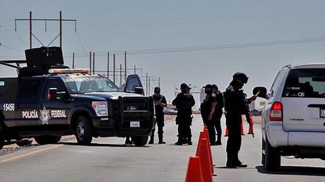 Un agente de la Policía Federal inspecciona un vehículo en un control de seguridad cerca de una prisión en Ciudad Juárez.