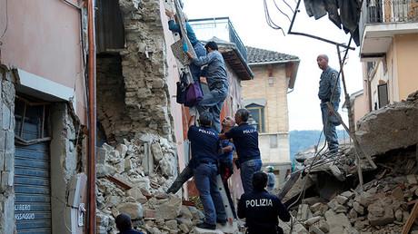 Un equipo de rescate ayuda a una mujer salir de su casa tras el terremoto en Amatrice, Italia, el 24 de agosto de 2016.