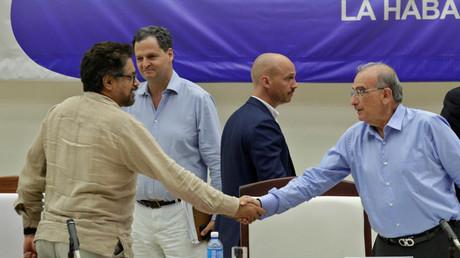 El jefe negociador del gobierno Humberto de la Calle (derecha) y el líder negociador de las Farc, Iván Márquez, estrechan las manos