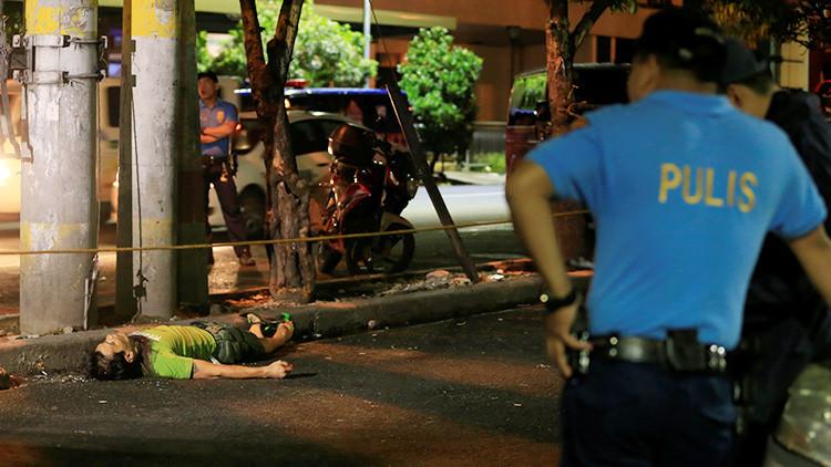 Agentes de la Policía Nacional de Filipinas cerca del cuerpo de un presunto traficante de drogas, que murió durante una operación policial en la ciudad de Malate.