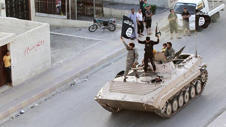 Combatientes sostienen la bandera del Estado Islámico durante un desfile militar en la provincia de Raqa