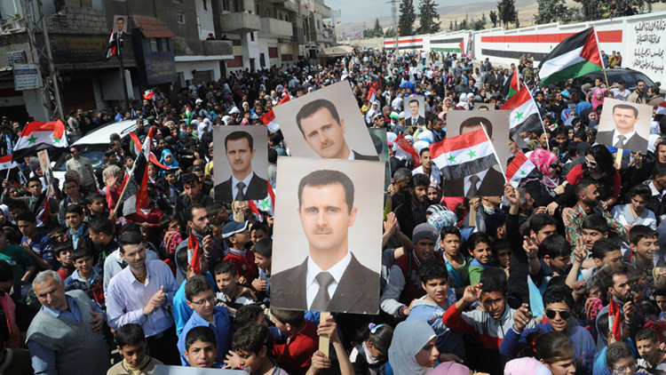 Ciudadanos sirios muestran su apoyo al presidente del país, Bashar al Assad y al Ejército sirio en la ciudad de Artouz, 19 de de marzo de 2014.