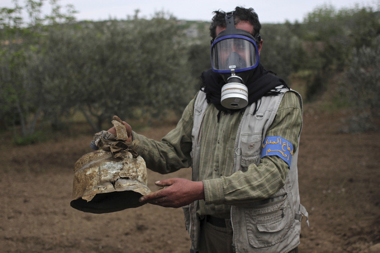 Un miembro de la Protección Civil siria sostiene un recipiente de gas cloro en el pueblo de Ibleen, Siria, 3 de mayo de 2015.