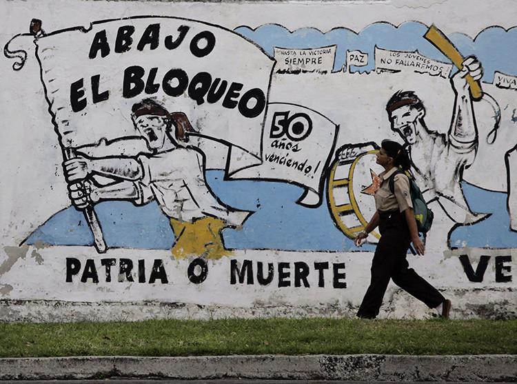 Una mujer camina en La Habana frente a un mural sobre el embargo económico de EE.UU. 26 de octubre de 2010.