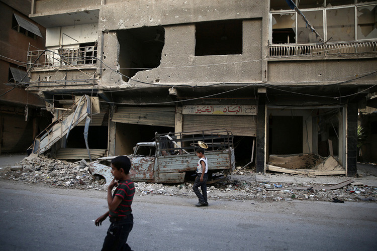 Niños pasean junto a edificios dañados en Damasco, Siria, el 17 de septiembre de 2016.