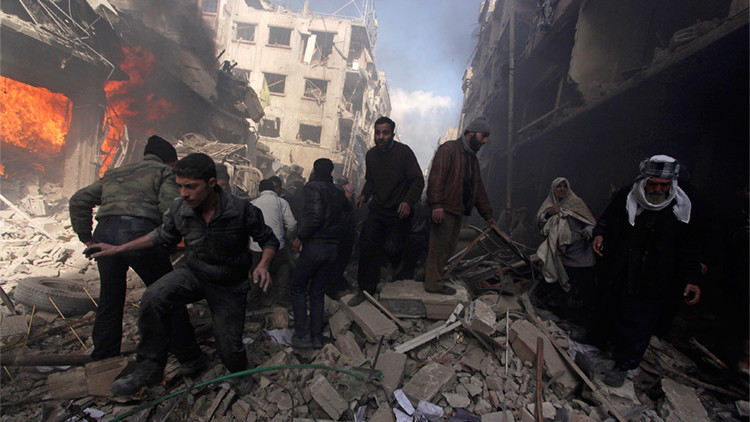 People walk on rubble as others try to put out a fire after what activists said were airstrikes and shelling by forces loyal to Syria's President Assad in Douma