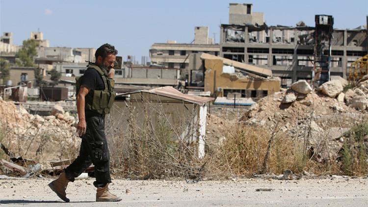 Un combatiente rebelde pasa junto a edificios dañados en Alepo, Siria.
