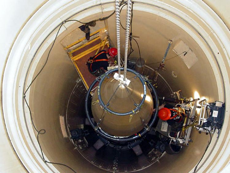 Técnicos de mantenimiento de la Fuerza Aérea quitan la sección superior de un misil intercontinental con la ojiva dentro