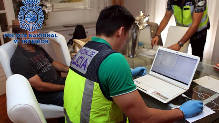 Agentes de la Policía Nacional analizando el material informático intervenido