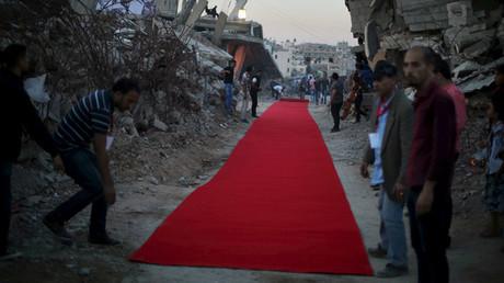 Los palestinos colocan una alfombra roja en las ruinas de los edificios antes de la muestra de una película sobre la guerra en la Franja de Gaza. Según los residentes locales, los edificios fueron destruidos por el ejército israelí en verano del 2014.