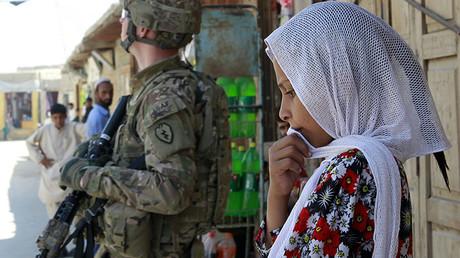 Una niña afgana permanece junto a un soldado estadounidense en Jalalabad, Afganistán. 5 de septiembre de 2011.
