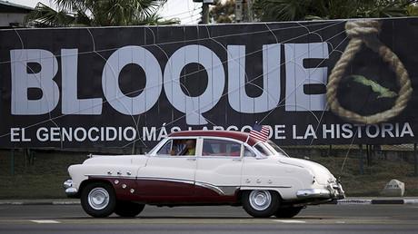 Un vehículo con la bandera estadounidense pasa frente a un cartel del embargo comercial de EE.UU. a Cuba. 20 de marzo de 2016.