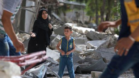 Una mujer se encuentra en medio de varios edificios destruidos por combates en el distrito de al-Qaterji en Alepo, Siria. 21 de septiembre de 2016.