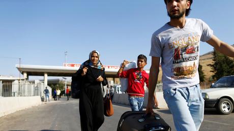 Los sirios entran en Turquía a través de un puesto fronterizo cerca de la localidad de Reyhanli, la provincia de Hatay (Turquía)