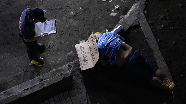 Un investigador de la Policía al lado del cuerpo de un hombre, con cinta envuelta alrededor de la cabeza y los pies. El policía dijo que el hombre es víctima de una ejecución vigilante relacionada con la droga en Manila.
